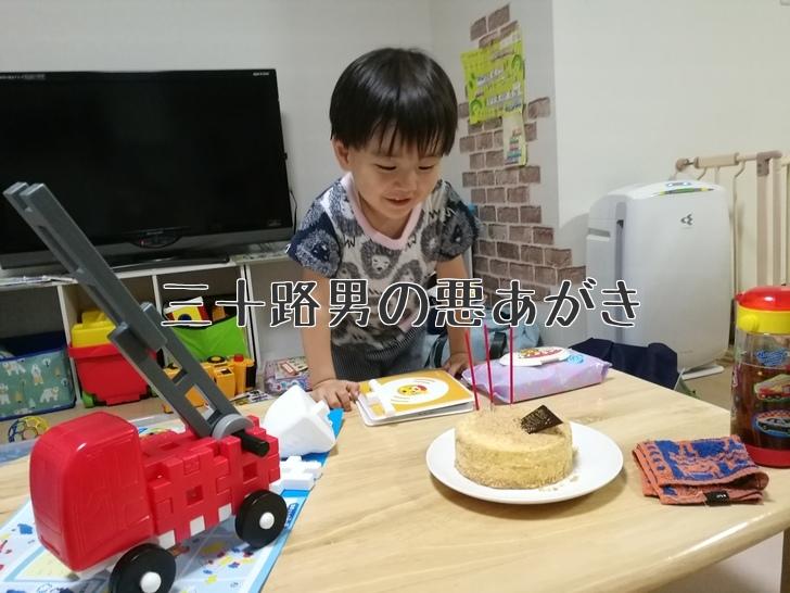 誕生日ケーキを見つめる3歳児