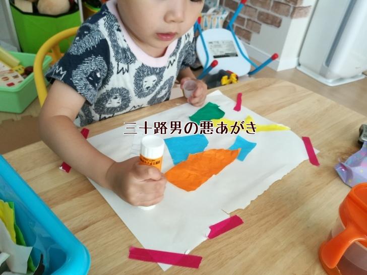 のりで折り紙を貼り付ける子供